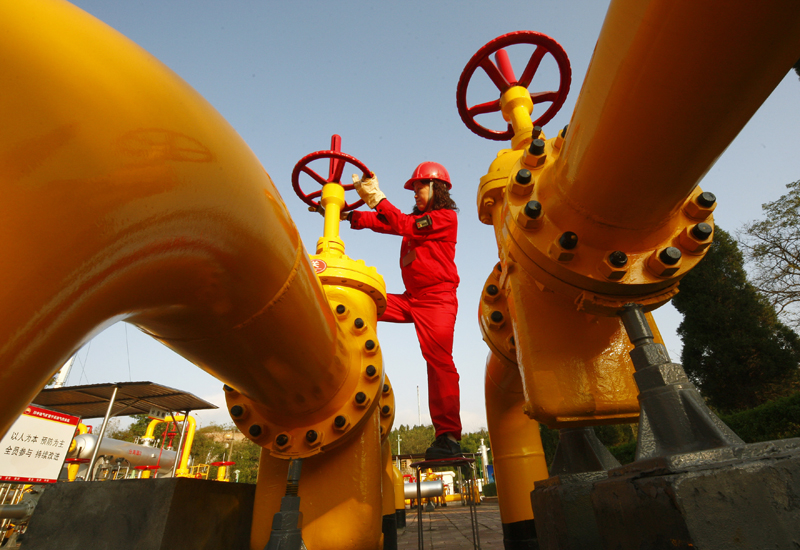 A Chinese worker checks a gas pipe at a natural gas plant in Suining, southwest China. GETTY IMAGES