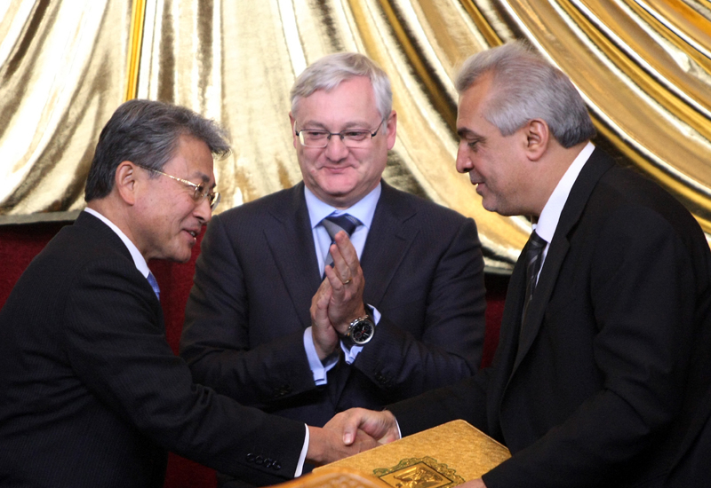 Shell CEO Peter Voser congratulating Iraq Oil Minister Abdul Kareem al-Luaibi and Mitsubishi's Tetsuro Kuwabara on signing the deal on 27 November. AH