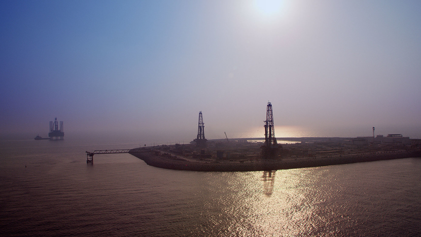 An artificial island, typically used to reduce cost by using land drilling instead of more expensive offshore rigs